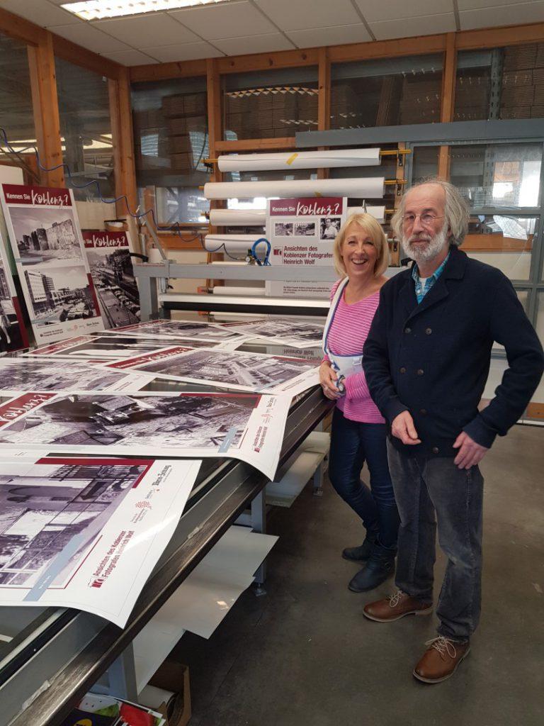 Beatrix und Martin Wolf neben Drucken für die Fotoausstellung über Ihren Vater Heinrich Wolf.